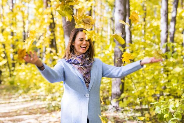 公園で紅葉で遊ぶ若い女性