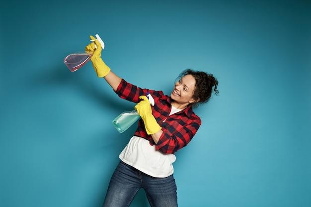 ピストルを撃つようにスプレーを掃除して遊んでいる若い女性。コピースペースで青の上にポーズをとる