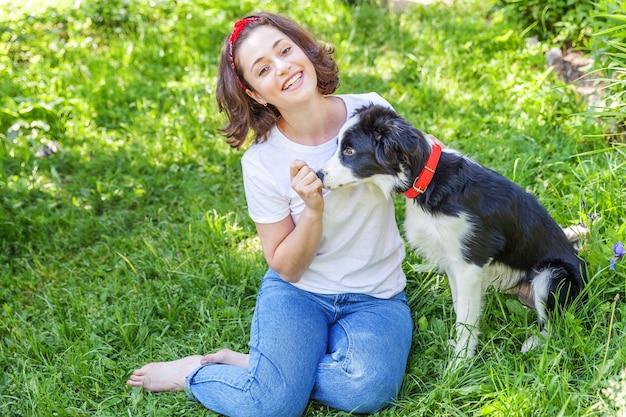 夏の庭や屋外の都市公園でかわいい子犬の犬のボーダーコリーと遊ぶ若い女性