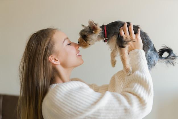 주말 날 집에서 강아지와 함께 재생하는 젊은 여자. 해피 요크셔 테리어 강아지