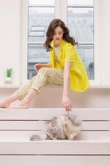 家で猫と遊ぶ若い女性。