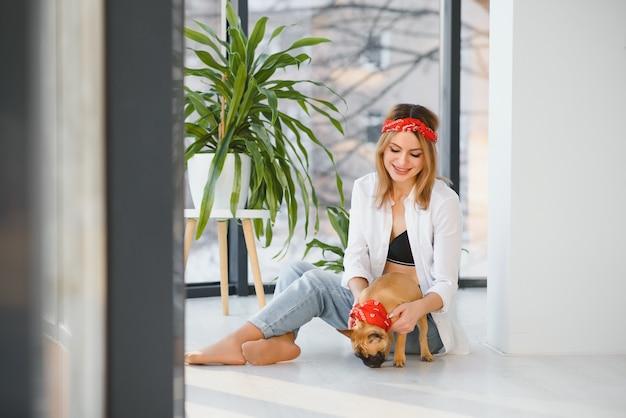 Молодая женщина играет со своей собакой дома
