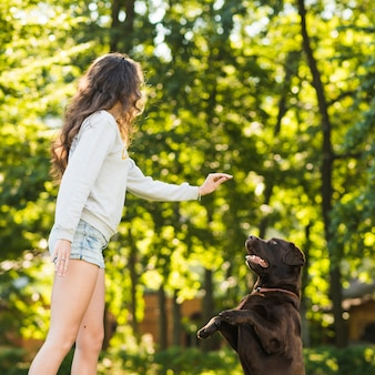 Young woman playing with her dog in garden