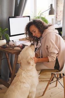 コンピューターと仕事で彼女の職場に座っている間彼女の犬と遊ぶ若い女性