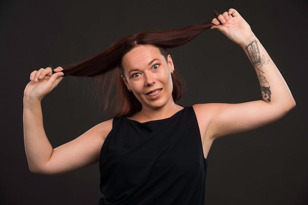 Молодая женщина, играя с ее волосами.