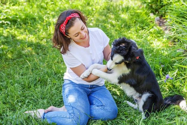 屋外の庭や都市公園で子犬の犬のボーダーコリーと遊ぶ若い女性