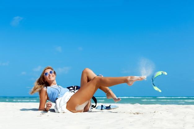 해변에서 모래를 가지고 노는 젊은 여자