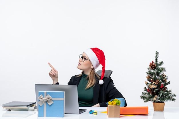 Giovane donna che gioca con il cappello di babbo natale e gli occhiali seduti a un tavolo con un albero di natale e un regalo
