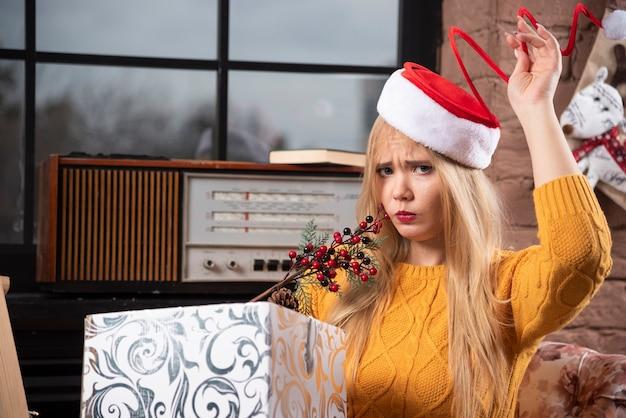 サンタの帽子で遊んで、カメラを見ている若い女性。