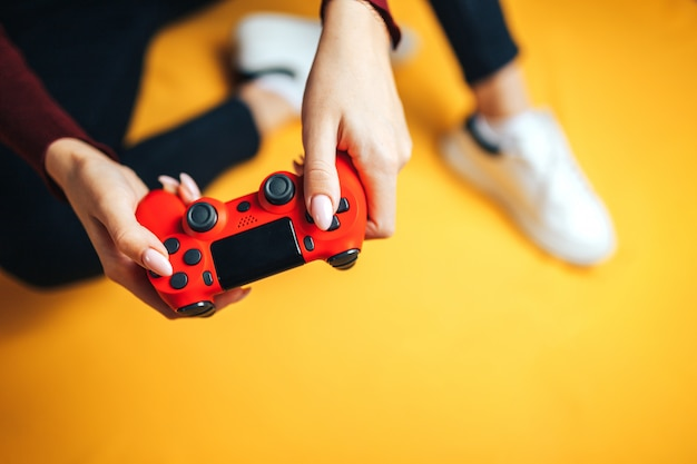 Young woman playing with two gamepads on yellow.