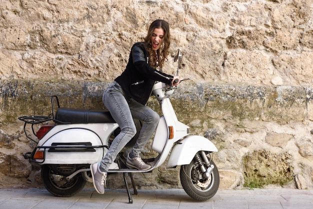 Young woman playing with a vintage motorbike