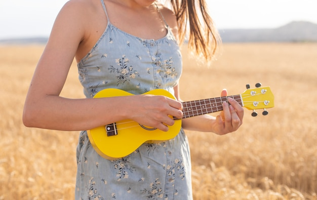 Young woman playing a yellow ukulele in a cereal field at sunset