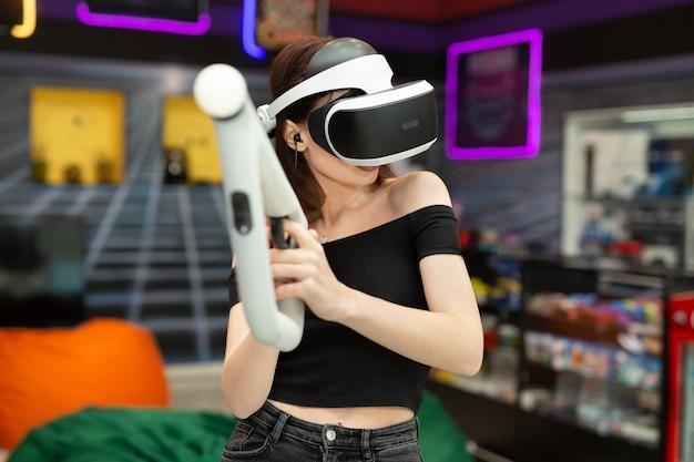 Молодая женщина играет на приставке, эмоциональный геймер снимает игру с помощью контроллера оружия в игровом клубе. vr