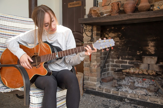 A young woman plays the guitar in a cozy atmosphere. the concept of hobbies and recreation.