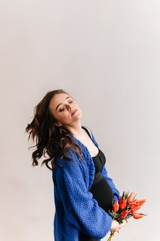Young woman plays hair on isolated background. pregnant brunette woman in blue cardigan holds tulips bouquet.