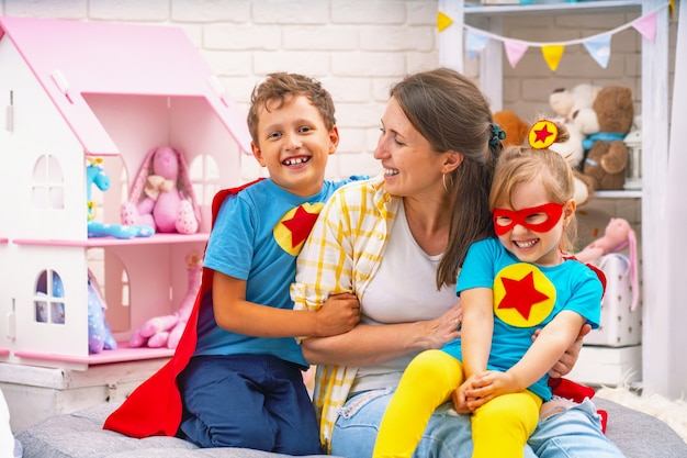 A young woman plays with her children in superheroes