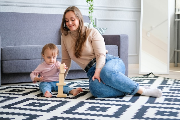 A young woman plays with her little daughter on the floor in the room