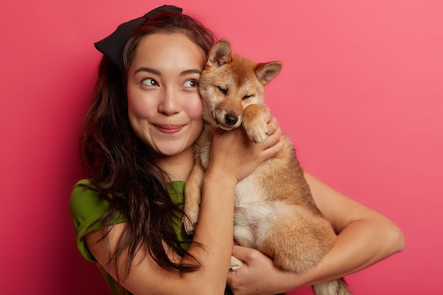 Young woman plays with lovely domestic pet, focused above with cheerful expression, comforts shiba inu dog, poses with devoted animal