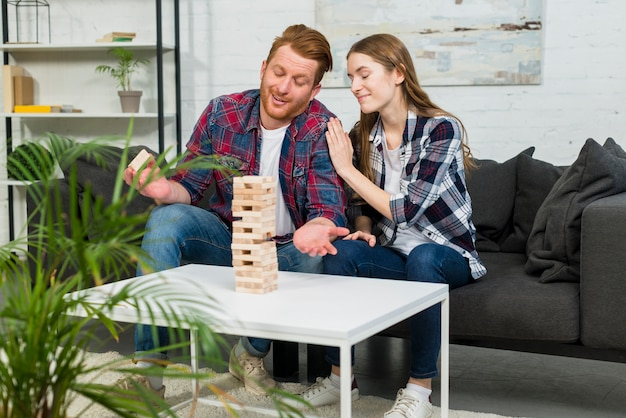 Young woman pleasing her boyfriend after removing the wooden block from tower at home