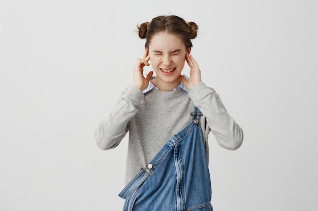 若い女性が耳を指で差し込み、不快に目をねじ込みます。会話を無視して聞いていない耳をカバーするブルネットの女性20代。