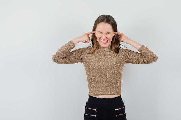 Giovane donna tappando le orecchie con le dita indice in maglione dorato e pantaloni neri e guardando tormentato, vista frontale.