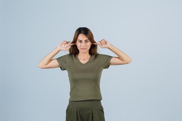 Молодая женщина затыкает шестерни пальцами в футболке, штанах и смотрит задумчиво, вид спереди.