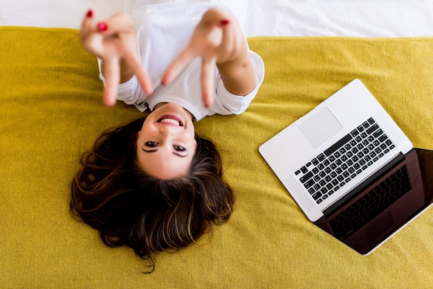 Young woman pointed victory sign lying in bed with laptop from above. top view.