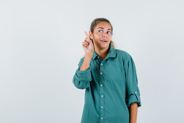 Young woman pointing aside in blue shirt and looking attentive