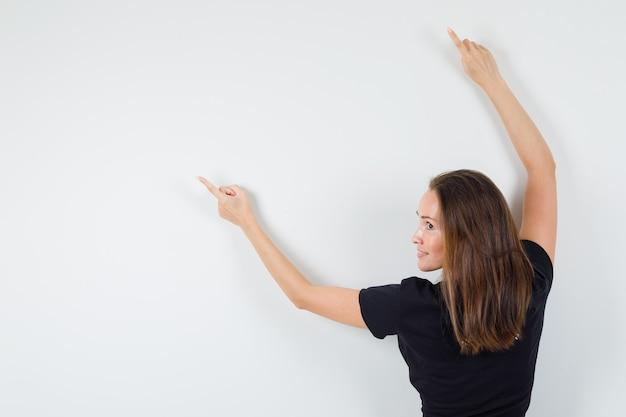 Молодая женщина, указывая в сторону, протягивая руки в черной блузке