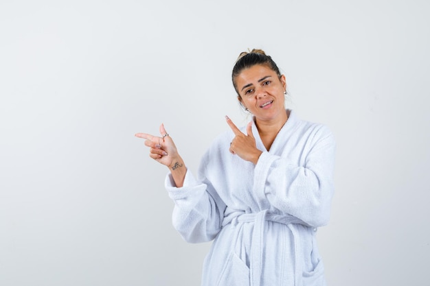 Молодая женщина указывая в сторону в халате и выглядит уверенно