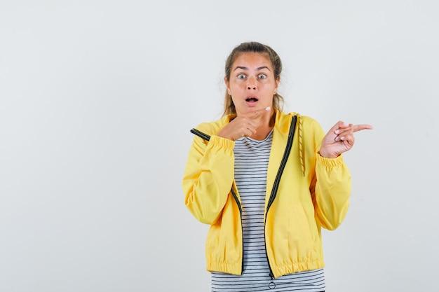 Tシャツ、ジャケットを脇に向けて驚いた若い女性。正面図。 無料写真