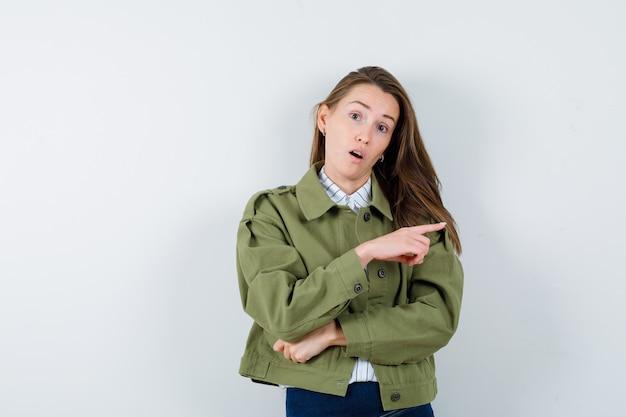 Giovane donna che indica da parte in camicia, giacca e guardando sorpreso, vista frontale.