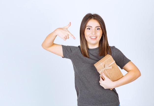 Молодая женщина, указывая на подарочную коробку указательным пальцем.