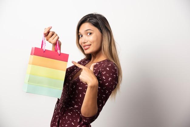 흰 벽에 작은 쇼핑 가방을 가르키는 젊은 여자.
