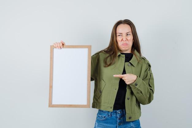 緑のジャケットの空白のフレームを指して、不満を探している若い女性。正面図。