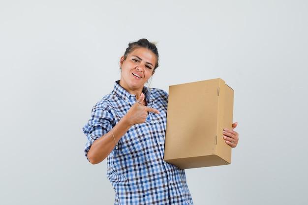市松模様のシャツのボックスを指して、陽気に見える若い女性。