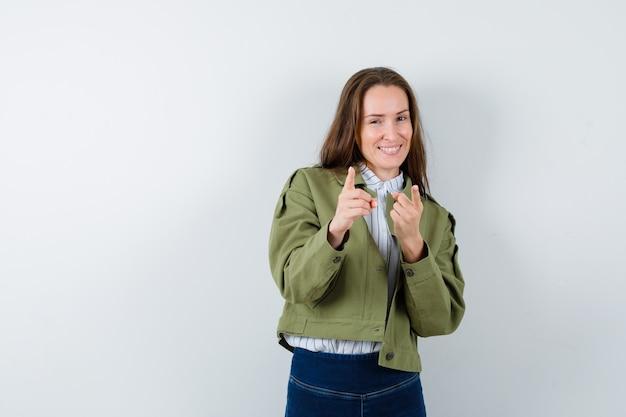 Молодая женщина, указывая на камеру в рубашке, куртке и рад, вид спереди.