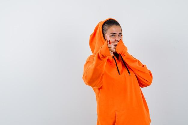 Молодая женщина указывая на камеру указательным пальцем в оранжевой толстовке с капюшоном и выглядит счастливой