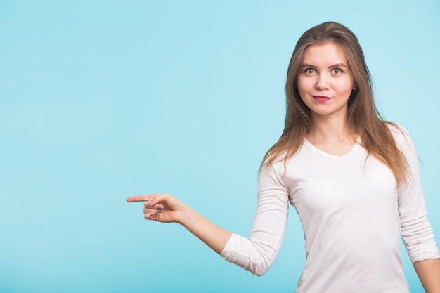 青い背景のコピースペースを指している若い女性