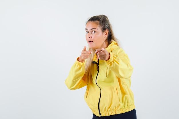 노란 우비에 정면을 가리키고 초점을 맞춘 젊은 여자
