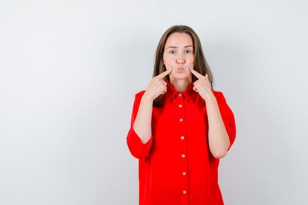 若い女性は彼女の頬を指して、赤いブラウスで唇をふくれっ面し、静かに見えます。正面図。