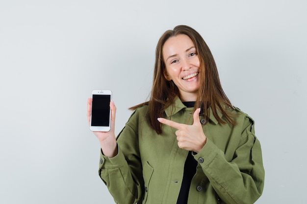 Молодая женщина, указывая на свой телефон в зеленой куртке и выглядя довольным, вид спереди.