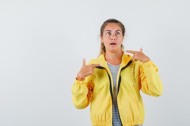 Tシャツ、ジャケットで自分自身を指して、驚いて見える、正面図の若い女性。