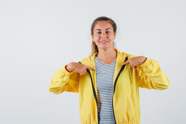 Tシャツ、ジャケットを着て、元気そうに見える若い女性。正面図。