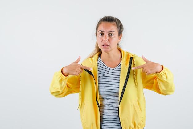 Tシャツ、ジャケットで自分自身を指して、混乱しているように見える若い女性、正面図。