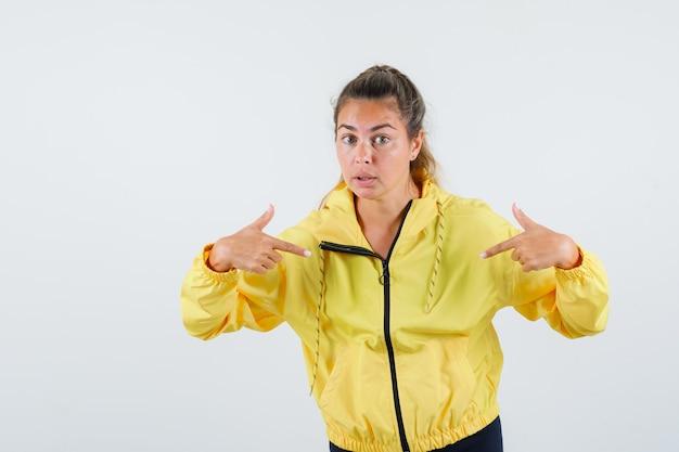 黄色いレインコートを着て自分を指さし、気配りのある若い女性