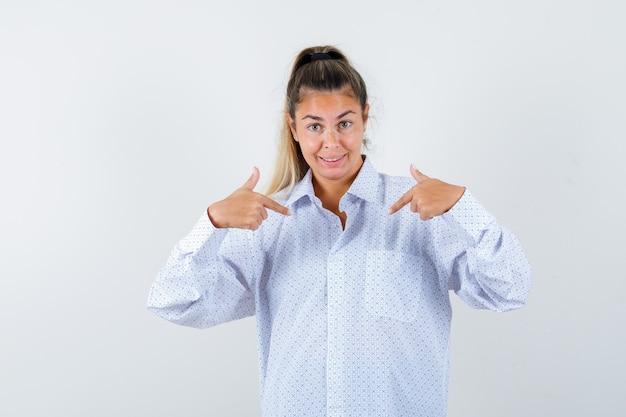 白いシャツの人差し指で自分を指して幸せそうに見える若い女性