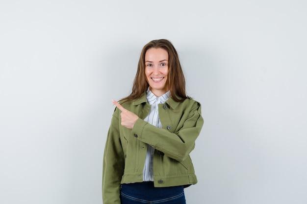 シャツ、ジャケットの左上隅を指して、陽気に見える若い女性、正面図。
