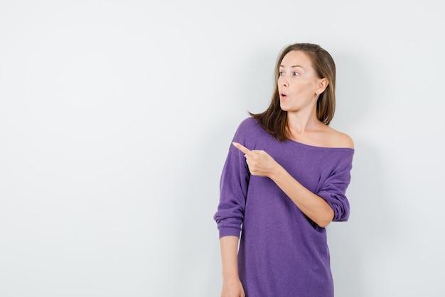 Молодая женщина указывая прочь в фиолетовой рубашке и выглядя изумленно. передний план.