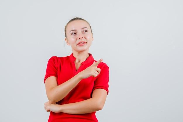 Giovane donna che indica via in maglietta rossa e che sembra speranzosa